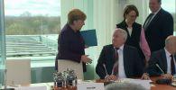 Канцлер ФРГ подошла к министру внутренних дел и протянула руку, но тот отказался пожать ее. Все засмеялись, в том числе сама Ангела Меркель.