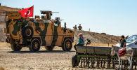 Сирийские местные жители наблюдают за турецкой военной машиной в ходе совместного патрулирования с американскими войсками в сирийской деревне аль-Хашиша на окраине города Таль-Абьяд на границе с Турцией