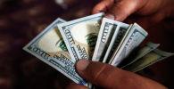 Мужчина пересчитывает 100 долларовые банкноты. Архивное фото