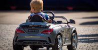 Ребенок катается на игрушечной машине. Архивное фото