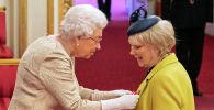 Королева Великобритании Елизавета II во время награждения командующего Орденом Британской империи Анне Крэйг в Букингемском дворце в Лондоне, 3 марта 2020 года