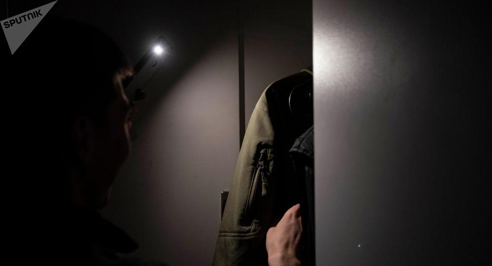 Мужчина светит фонарем мобильного телефона в темноте. Архивное фото