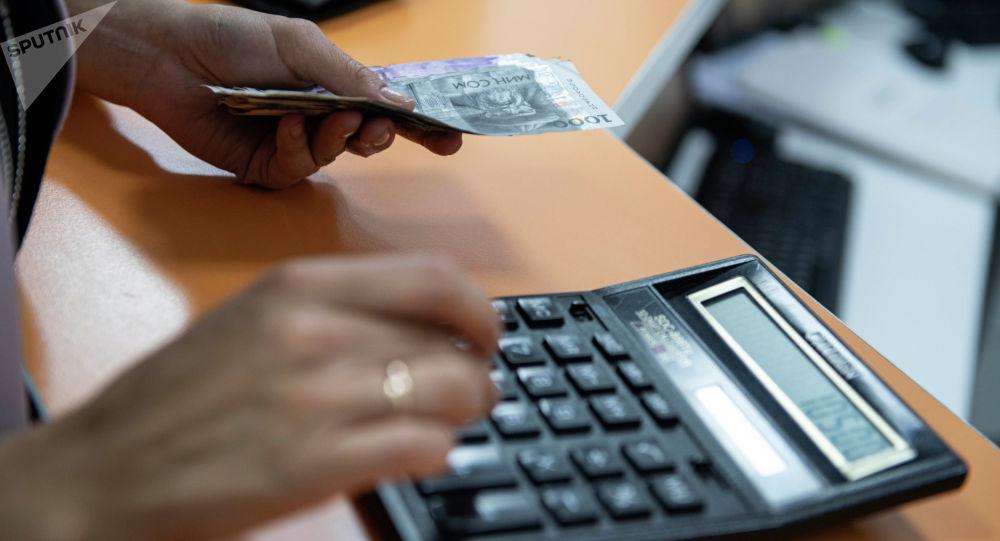 Девушка в одной руке держит деньги, а в другой считает на калькуляторе. Иллюстративное фото