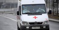 Медицинские работники в защитных костюмах в машине скорой помощи в Москве. Архивное фото