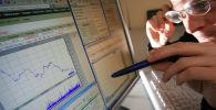 Мужчина с удивлением рассматривает показатели графика биржи. Архивное фото