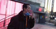 Пекинде чылым чеккен киши. Архивдик сүрөт