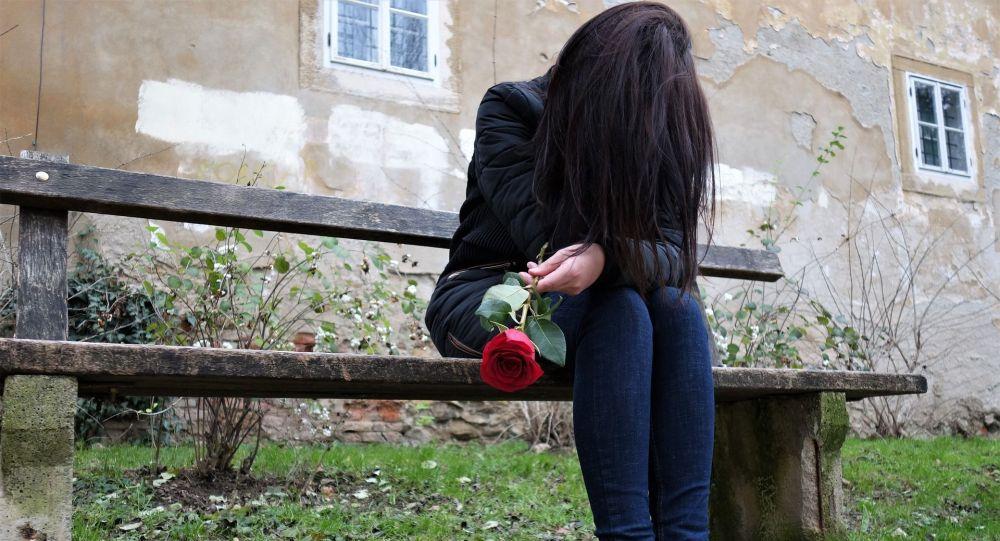 Девушка плаче сидя на скамейке. Архивное фото