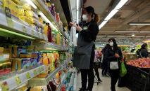 Сотрудница супермаркета в медицинской маске раскладывает товары на витрину. Архивное фото