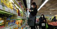 Сотрудница супермаркета раскладывает товары на полку. Архивное фото