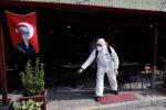 Работник муниципалитета в защитном костюме дезинфицирует кофейню возле пограничного перехода Пазаркуле в Турции с греческими Кастансами