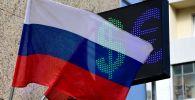 Флаг России на фоне табло курса валют. Архивное фото