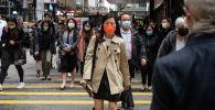 Горожане в защитных масках на одной из улиц в Гонконге.