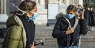 Девушки в масках на одной из улиц Милана. Архивное фото