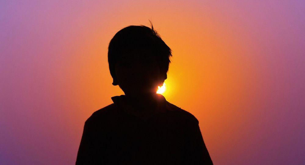 Силуэт мальчика на закате. Иллюстративное фото