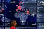 Женщина проходит мимо карты мира, на которой показаны страны, зараженные новым коронавирусом COVID-19, во время пресс-конференции в штаб-квартире Национальной полиции в Панама-Сити. 10 марта 2020 года