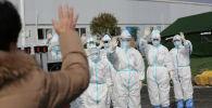 Медицинский персонал в защитных костюмах машут пациенту, который выписывается из больницы после выздоровления от коронавируса в провинции Ухань, Китай