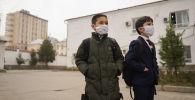Школьники в медицинских масках в одном из школ Душанбе. Архивное фото
