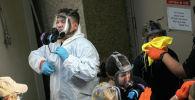 Бригада уборщиков снимает защитную одежду после дезинфекции помещения. Архивное фото