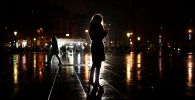 Женщина смотрит на смартфон на городской площади. Архивное фото