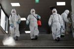 Рабочие, носящие защитное снаряжение, дезинфицируют в качестве меры предосторожности против нового коронавируса на станции метро в Сеуле, Южная Корея, в пятницу, 13 марта 2020 года.