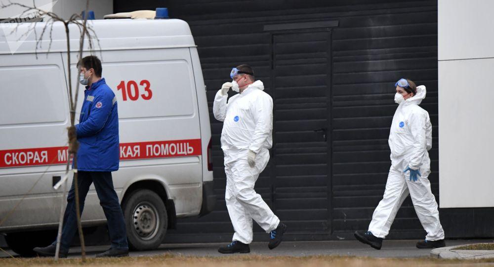 Сотрудники скорой помощи в защитных костюмах на территории больничного комплекса. Архивное фото