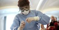 Медицинский работник готовится взять образцы для теста на коронавирус. Архивное фото