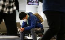 Медициналык маска кийген аэропорттогу жүргүнчү