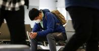 Эл аралык аэропортунда жүргүнчү медициналык бет капчан отурат. Архив