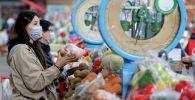 Алматынын базарында бет кап кийип соода кылып жүргөн аял. Архивдик сүрөт