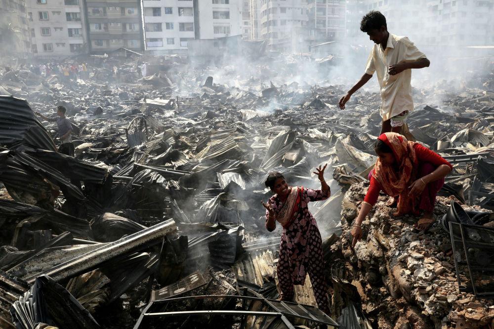 Обитатели трущоб в столице Бангладеш, Дакке, ищут предметы домашнего обихода, сохранившиеся после пожара