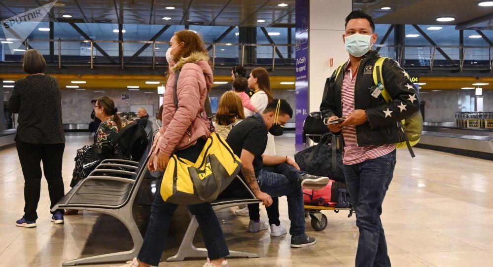 Жүргүнчүлөр коопсуз бет капчапн эл аралык аэропортунда. Архив