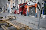 Пара в масках идет вдоль закрытых баров и ресторанов рядом со Старым портом в Марселе, на юге Франции, после того как все второстепенные общественные места, включая рестораны и кафе, были закрыты для предотвращения распространения COVID- 19, вызванный новым коронавирусом. 16 марта 2020 года