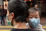 Ребенок в защитной маске на руках отца на одной из улиц в Гонконге. Архивное фото