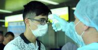 Медицинский работник проверяет прибывшего гражданина на коронавирус. Архивное фото