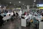 Медицинский персонал в защитном снаряжении проверяют пассажиров в качестве профилактической меры против коронавируса. Архивное фото