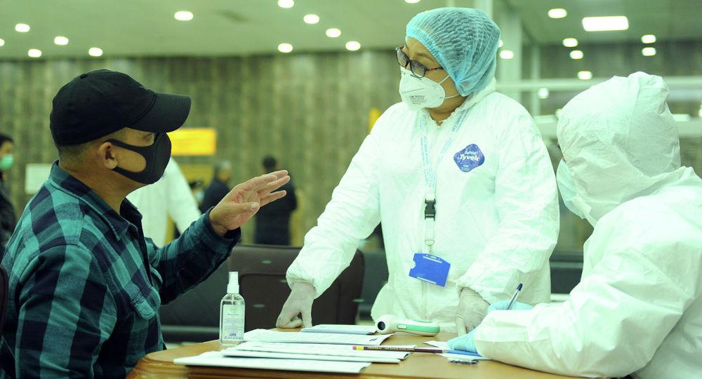Аэропортто жүргүнчүлөрдү тозуп жаткан медицина кызматкерлери. Архив
