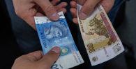 Купюры номиналом 100 сомов и 100 рублей. Архивное фото