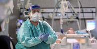 Медицинский работник в защитной маске и костюме и пациент, страдающий коронавирусной болезнью (COVID-19), находятся в отделении интенсивной терапии больницы Oglio Po в Кремоне. Италия, 19 марта 2020 года