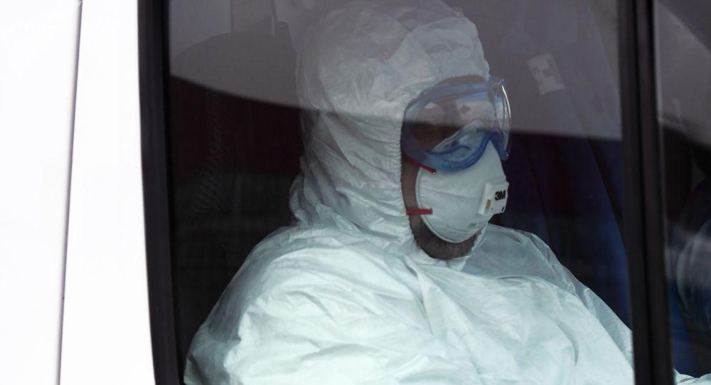 Медицинский работник в защитном костюме в машине скорой помощи. Архивное фото