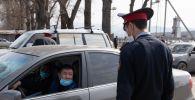 Сотрудник автоинспекции проверяет автомобиль на блокпосту. Архивное фото