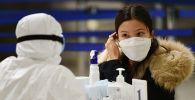 Медицинский работник проверяет состояние пассажира в аэропорту.  Архивное фото