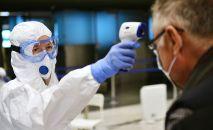 Медицинский работник измеряет температуру пассажиру в аэропорту. Архивное фото