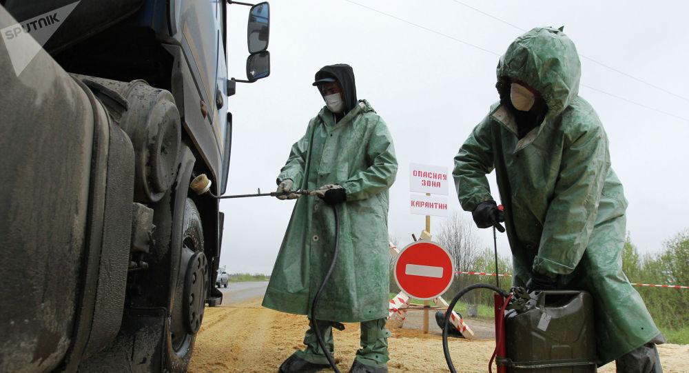 Сотрудники санитарных служб обрабатывают грузовик дезинфицирующим раствором. Архивное фото