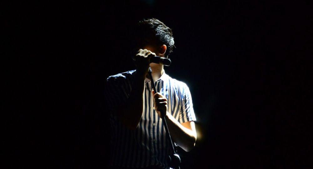 Выступление молодого артиста с микрофоном. Иллюстративное фото