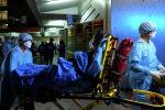 Медработники носят средства индивидуальной защиты и несут пациента в носилках на машине скорой помощи в Fu Heng Estate, в Гонконге. Китай 14 марта 2020 года