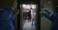 Медицинский персонал прощается с выздоровевшим пациентом с коронавирусом COVID-19 в больнице Красного Креста в Ухане, Китай. 16 марта 2020 года