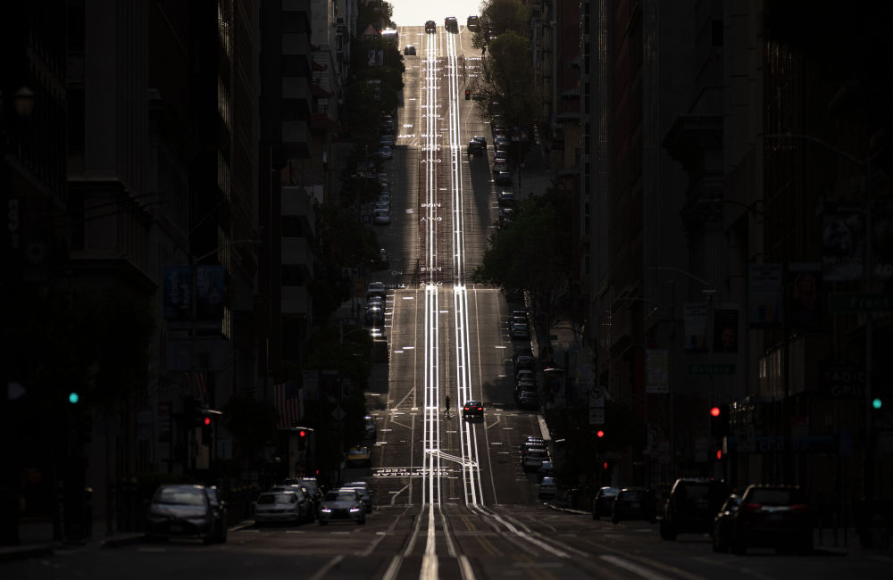 Калифорния-стрит, обычно заполненная канатными дорогами, видна пустой в Сан-Франциско, штат Калифорния, 18 марта 2020 года