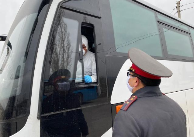 Сотрудники медицинской службы и правоохранительных органов во время встречи вернувшихся из Египта и Таиланда кыргызстанцев