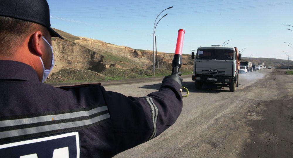 Сотрудник патрульной службы на санитарно-карантинном блокпосту на въезде в Ош (со стороны Жапалакской территориальной управы)