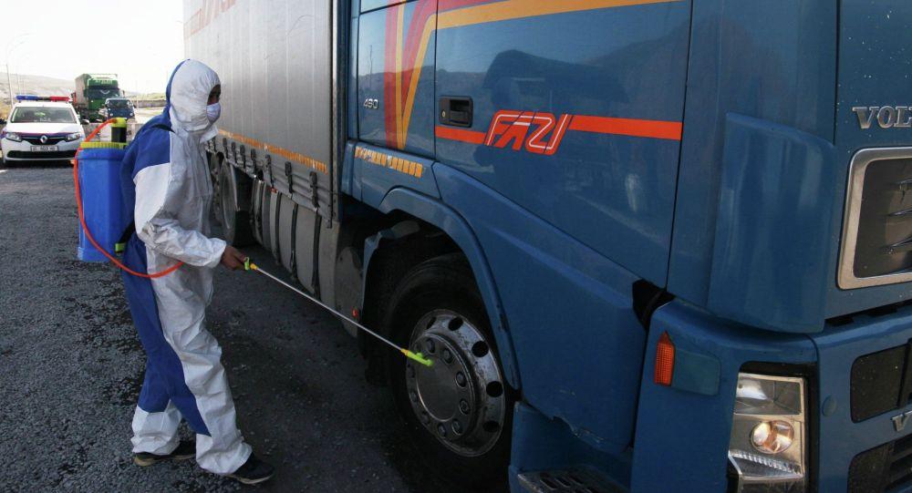 Сотрудник санэпидстанции и МЧС КР проводит дезинфекцию автотранспорта на санитарно-карантинном блокпосту на въезде в Ош со стороны Жапалакской территориальной управы.